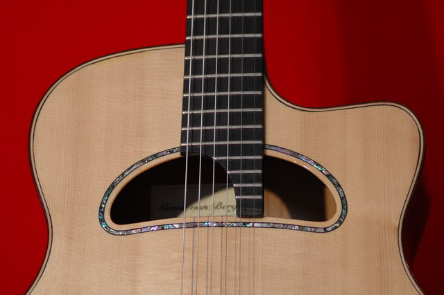 The wide soundhole, fingerboard with 24 frets